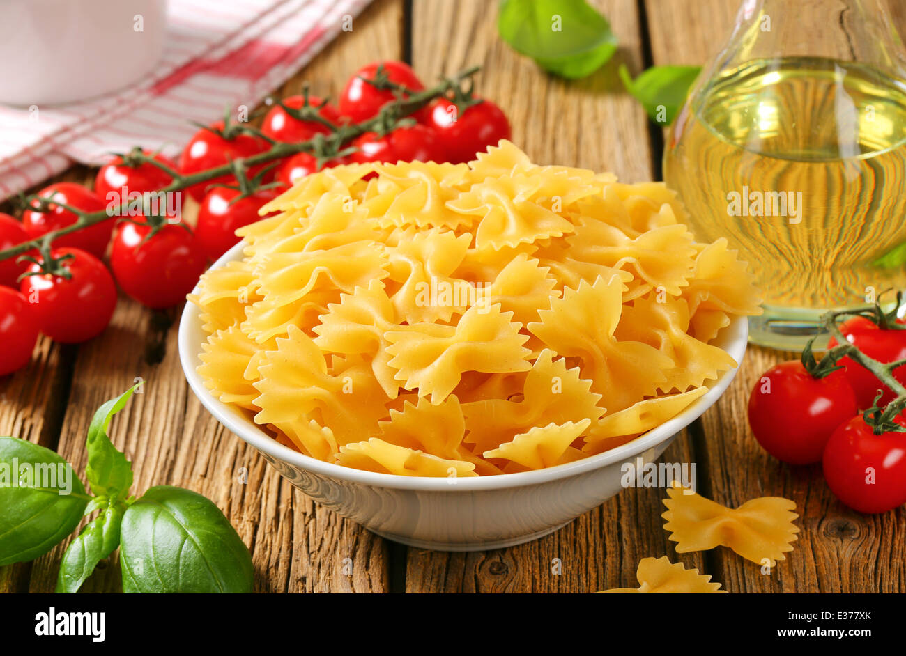 Uncooked bow tie pasta and other ingredients - Stock Image