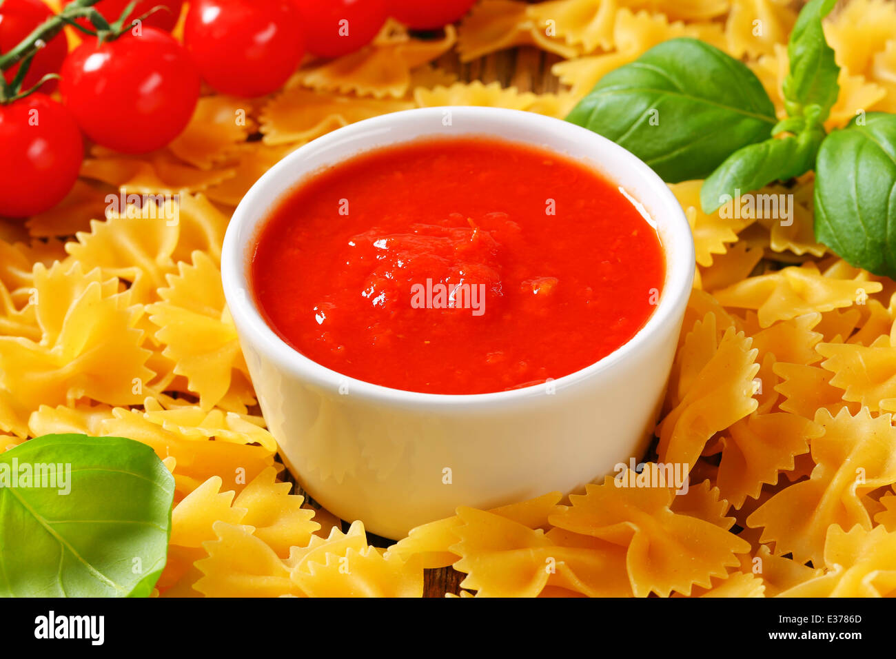 Uncooked bow tie pasta and tomato puree - Stock Image