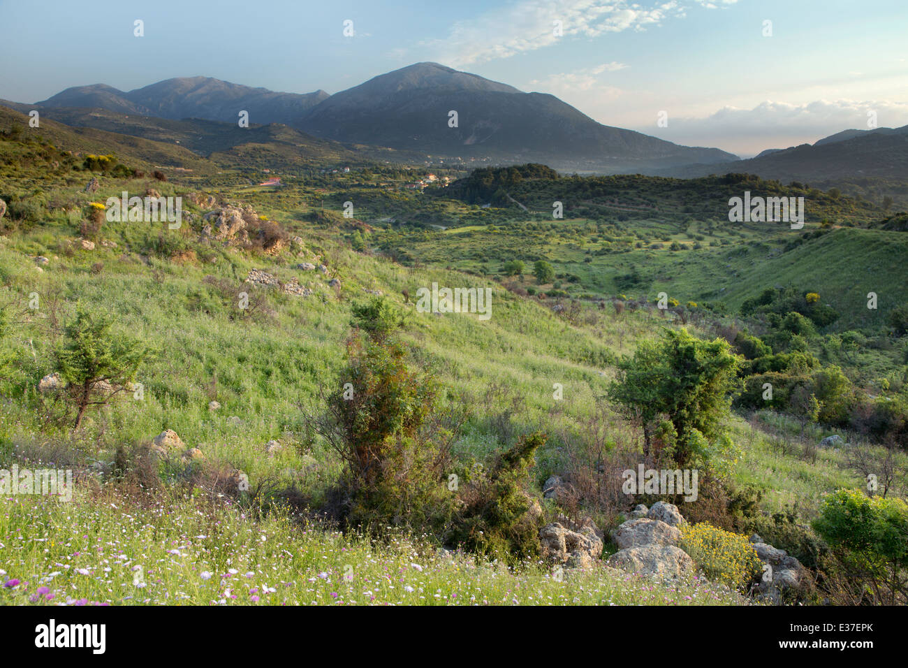 Landscape photograph of the sun rising and casing a warm light over the mountain and village at Agia Eirini, Kefalonia Stock Photo