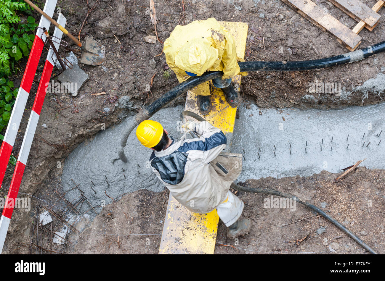 Construction workers pour concrete into a ditch. Rainy weather. Bird's eye view. Stock Photo