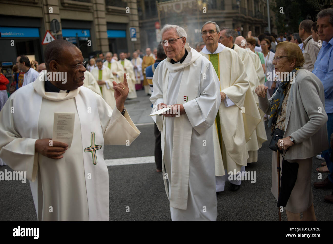 Barcelona, Spain. 22nd June, 2014. A priest talks to a woman during a religious procession in the streets of Barcelona. - Stock Image