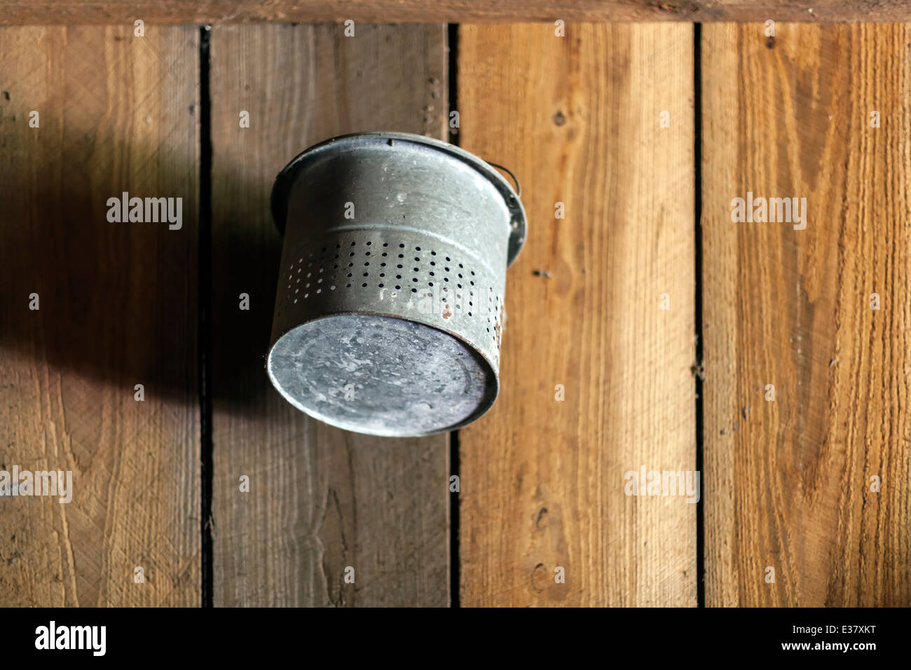 Old galvanized steel bucket or pail hanging on the wooden wall of an old barn. USA - Stock Image