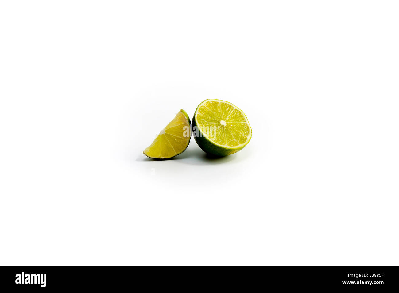 Lime half and lime slice in field of white. Optional cutout. - Stock Image