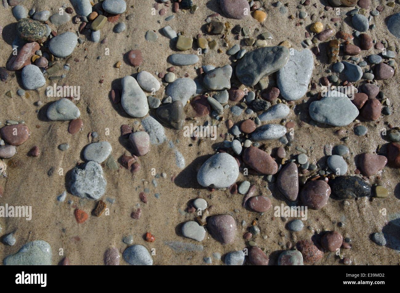 Detail of a wet sandy beach with smooth pebbles at soft lighting - Stock Image