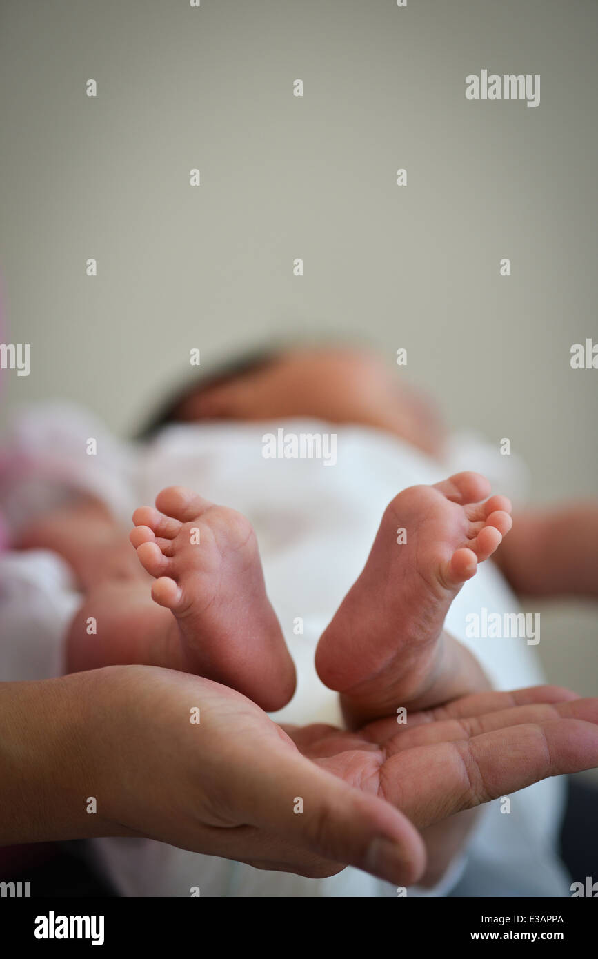 Baby Infant Precious Feet Over Mother's Hand - Innocence Concept - Stock Image