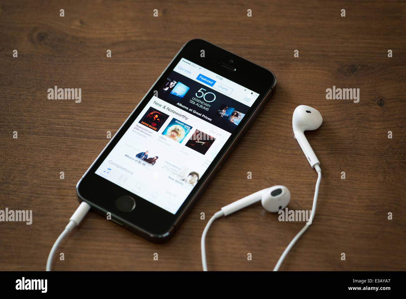 Brand new Apple iPhone 5S with iTunes store application on the screen lying on a desk with headphones Stock Photo