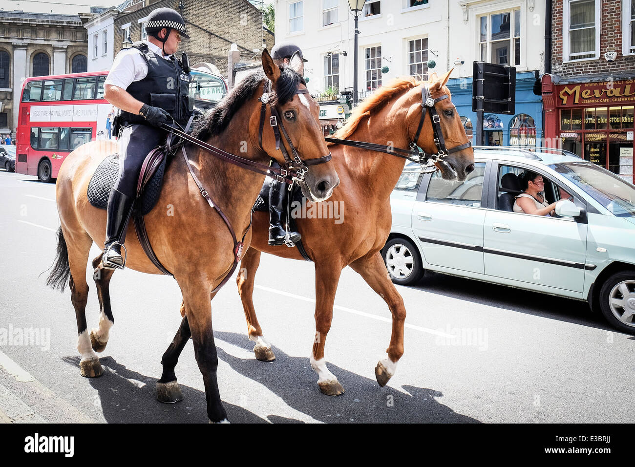 Two mounted Metropolitan Police Officers patrolling the street of Greenwich. - Stock Image