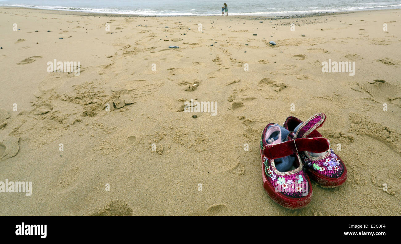 Abandoned child's shoes on a beach. - Stock Image
