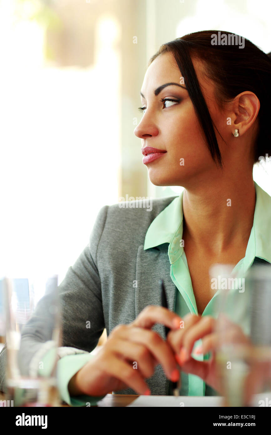 Portrait of a pensive businesswoman looking away in office - Stock Image