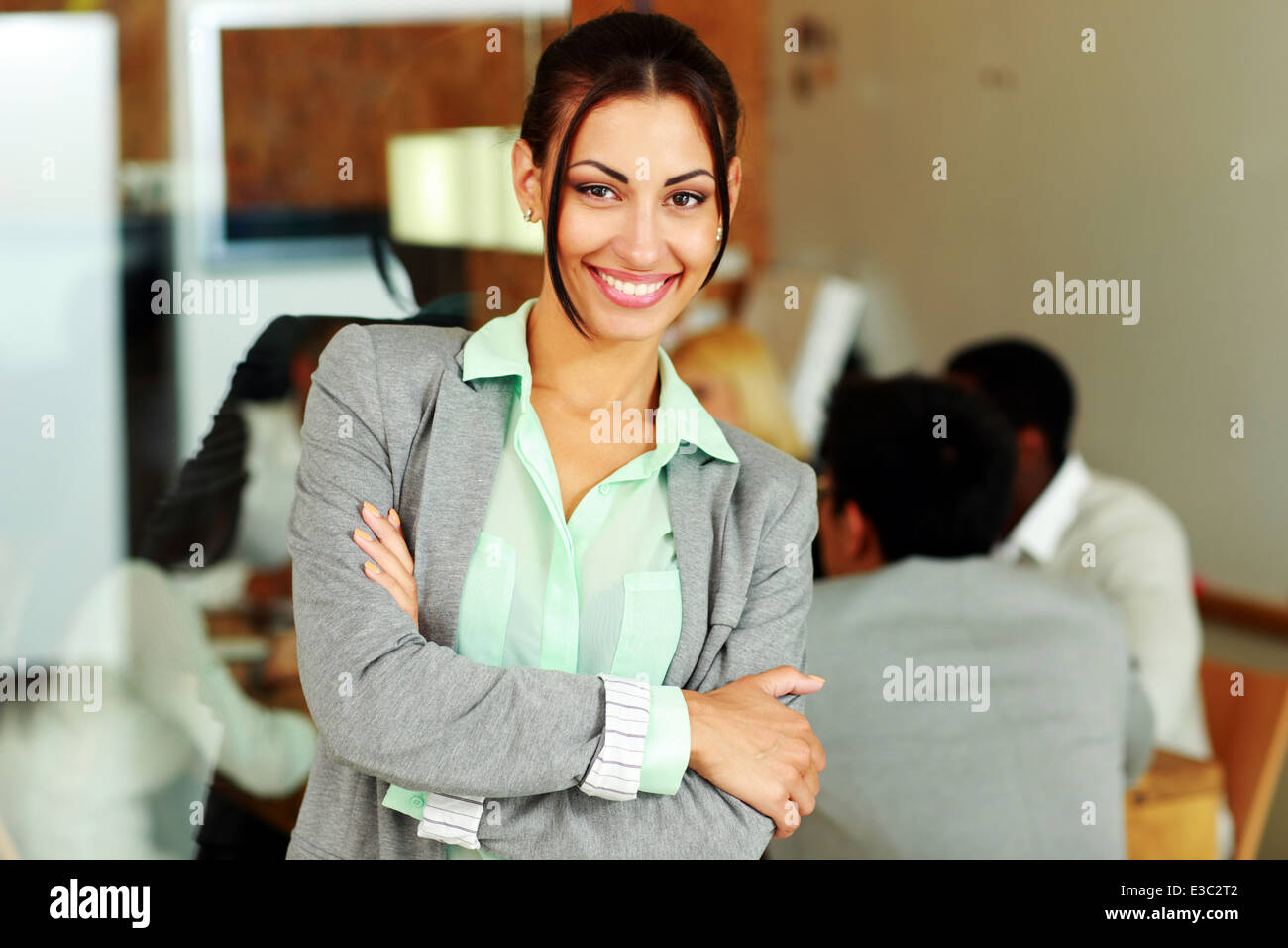 Happy businesswoman with arms folded standing in front of colleagues - Stock Image