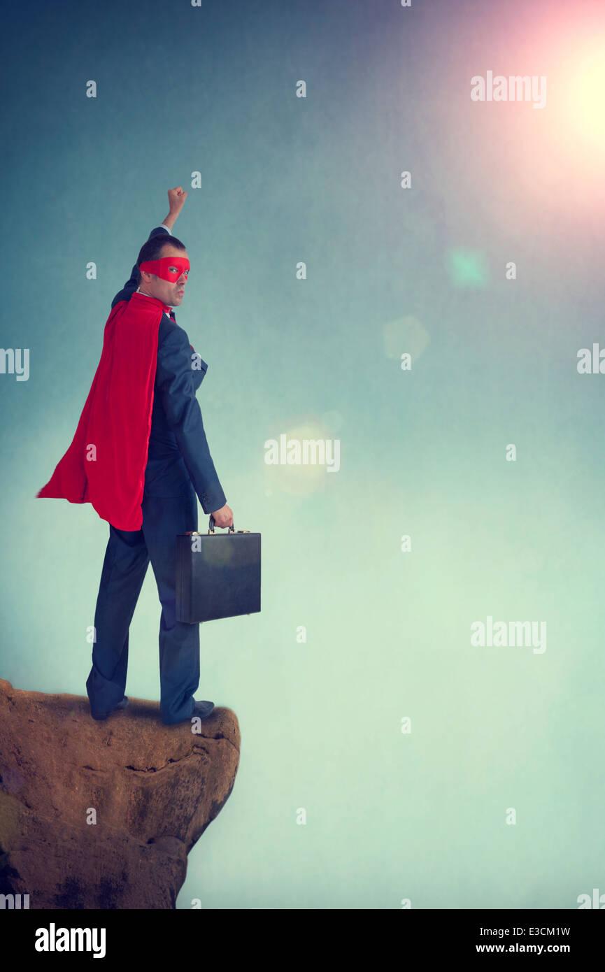 superhero businessman standing on a cliff edge pumping fist - Stock Image