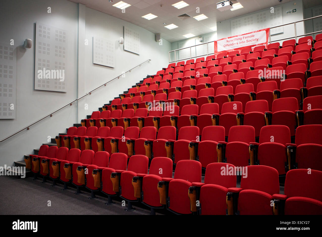An empty university lecture theatre with red seats - Stock Image