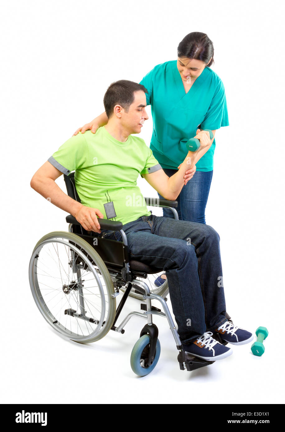 Physical therapist works with patient in lifting hands weights. Young adult in wheelchair. - Stock Image