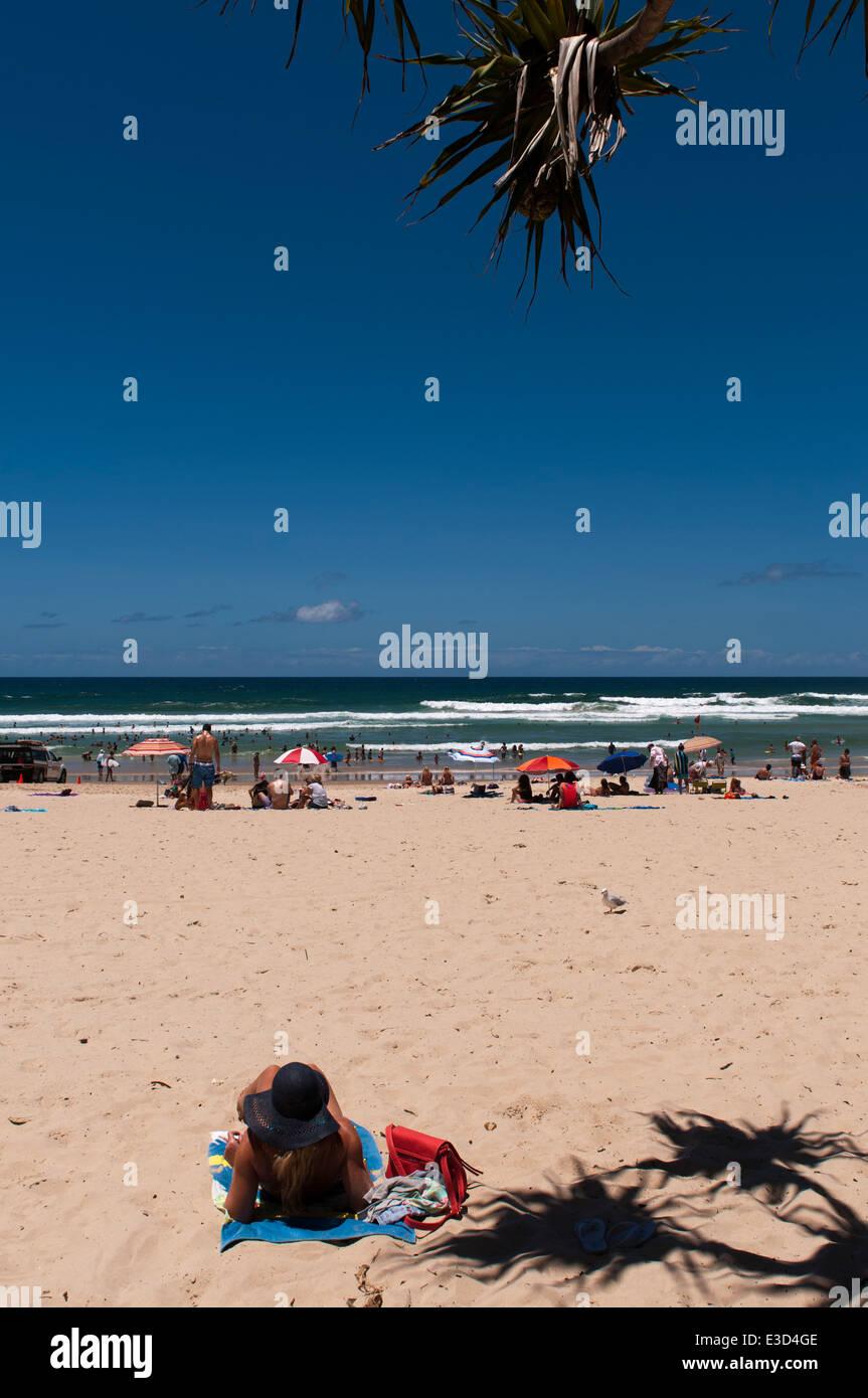 Woman sunbathing on Kirra Beach, Gold Coast, Queensland. - Stock Image