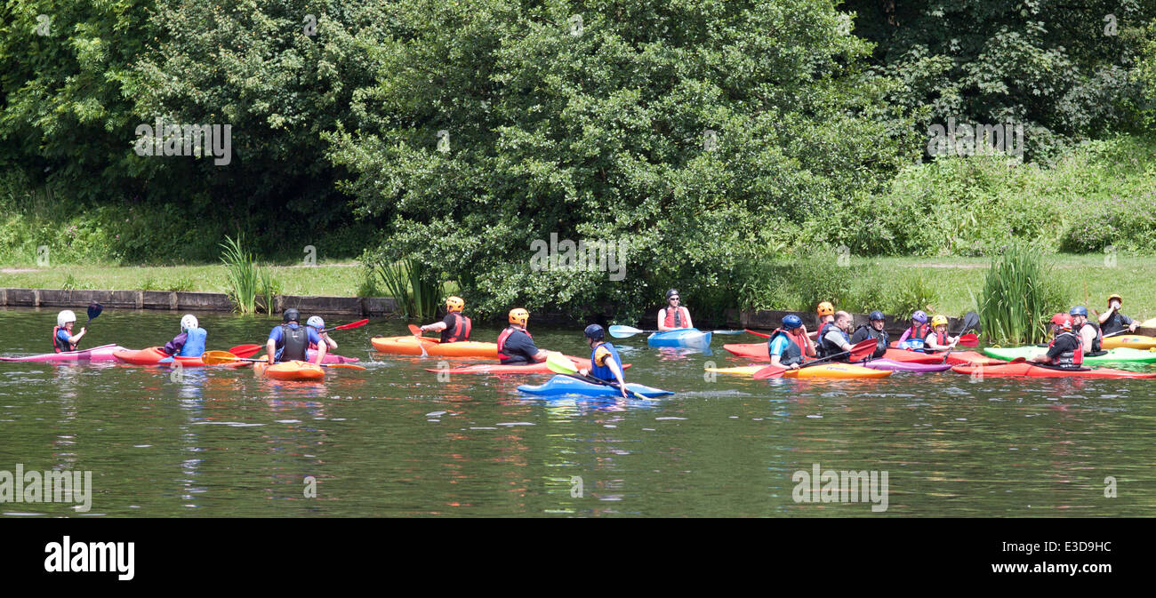 Children and instructors canoeing/kayaking  on the lake in Yarrow Valley Country Park, Coppull in Lancashire, UK. - Stock Image