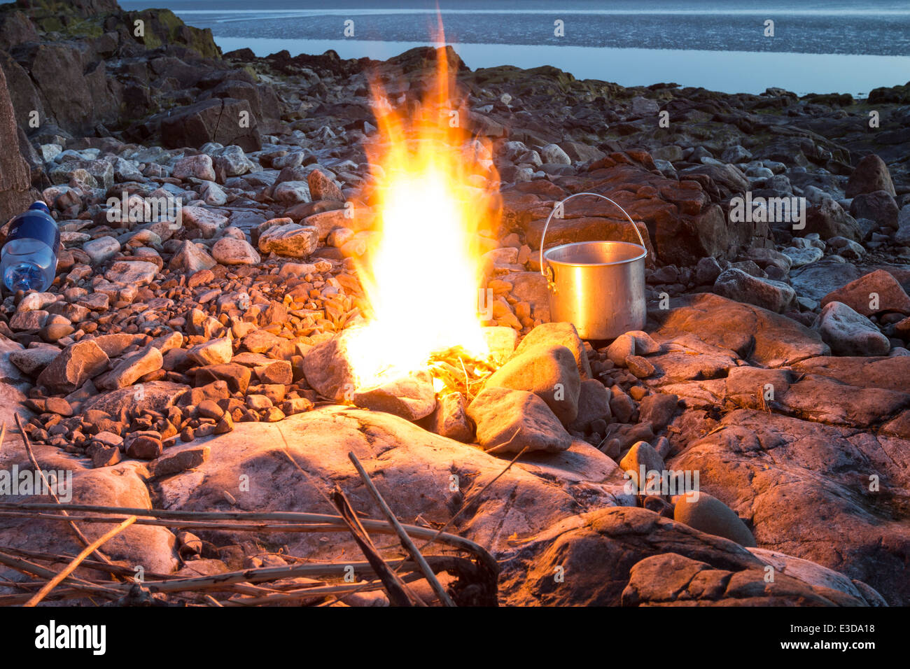 Camp Fire with Cooking Pot on a Rocky Beach at Dusk England UK - Stock Image