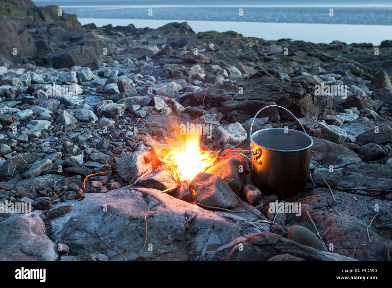 Fire with Cooking Pot on a Rocky Beach England UK - Stock Image