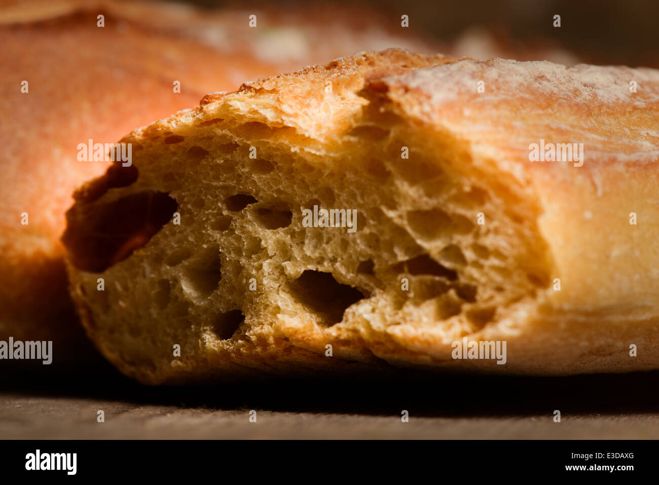 French crusty bread, isolated on a wooden plank background - Stock Image