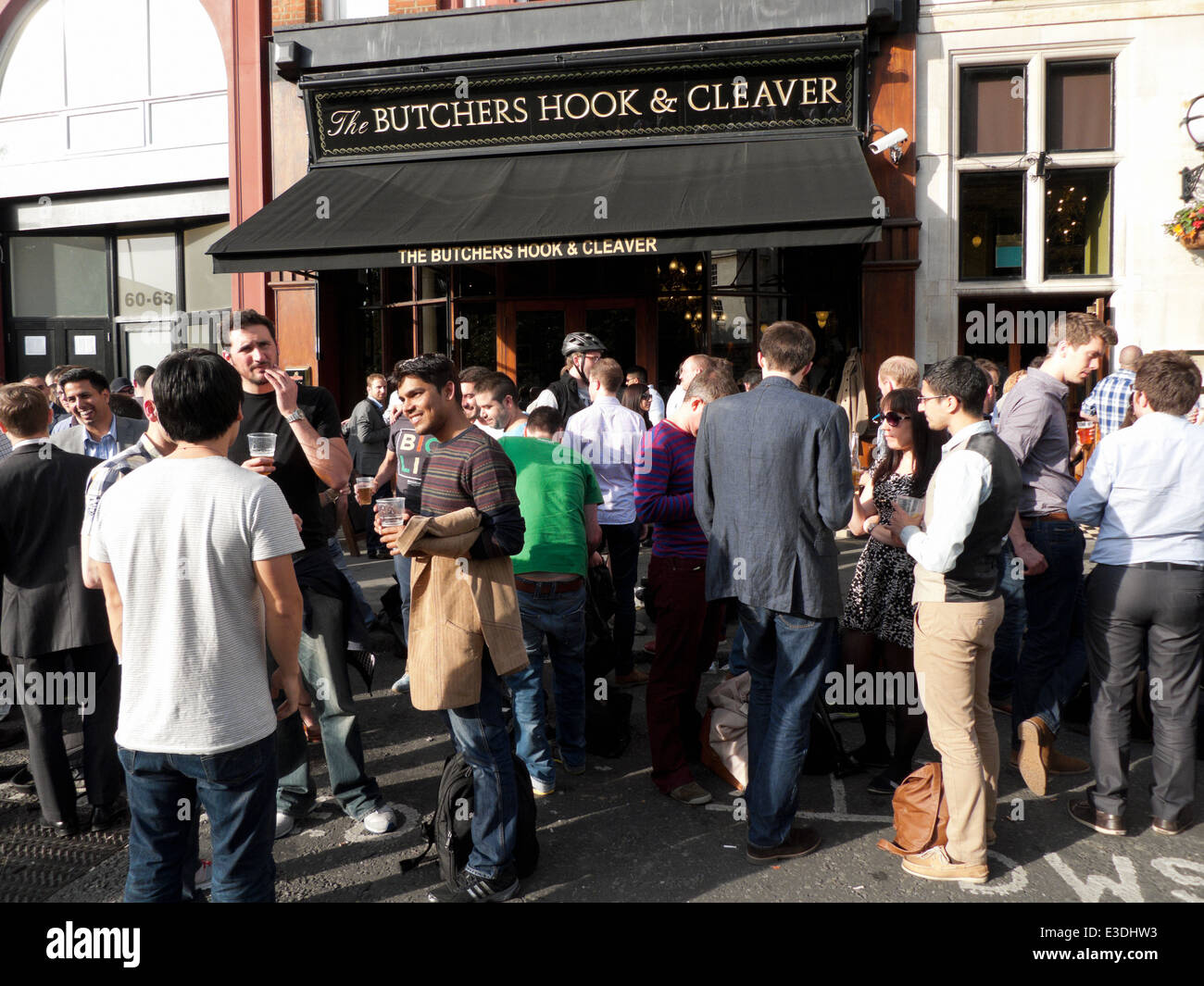Work colleagues having a beer on the pavement outside The Butchers Hook & Cleaver pub near St Barts Hospital - Stock Image