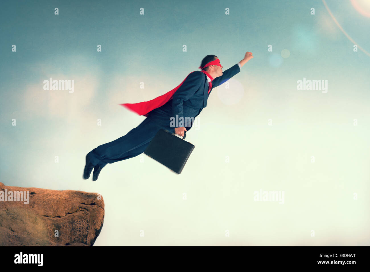 superhero businessman taking off to flight from a cliff ledge wearing a cape and mask - Stock Image