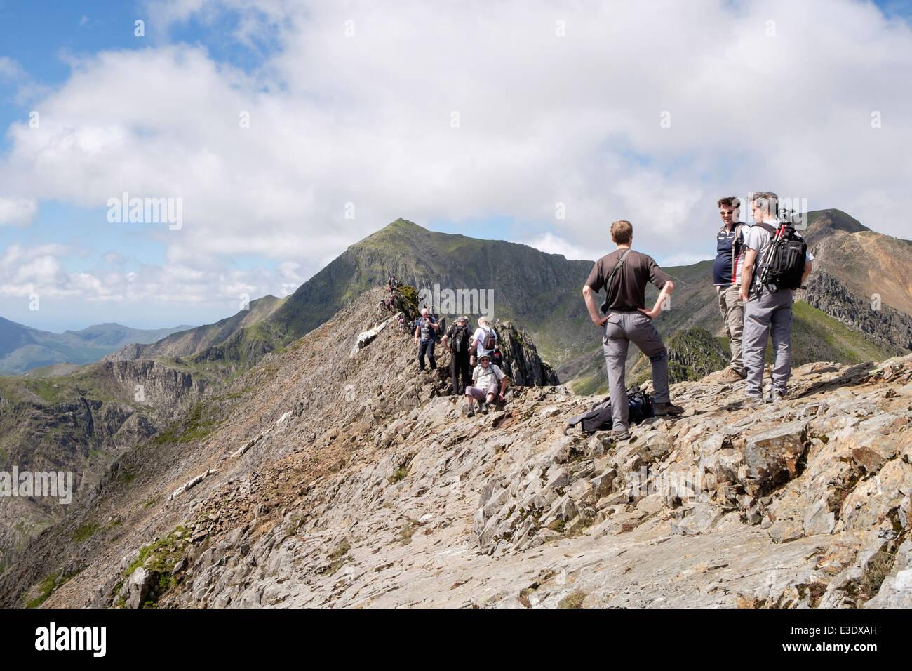 Hikers on Crib Goch knife edge ridge top scramble at start of Mount Snowdon Horseshoe in mountains of Snowdonia Stock Photo