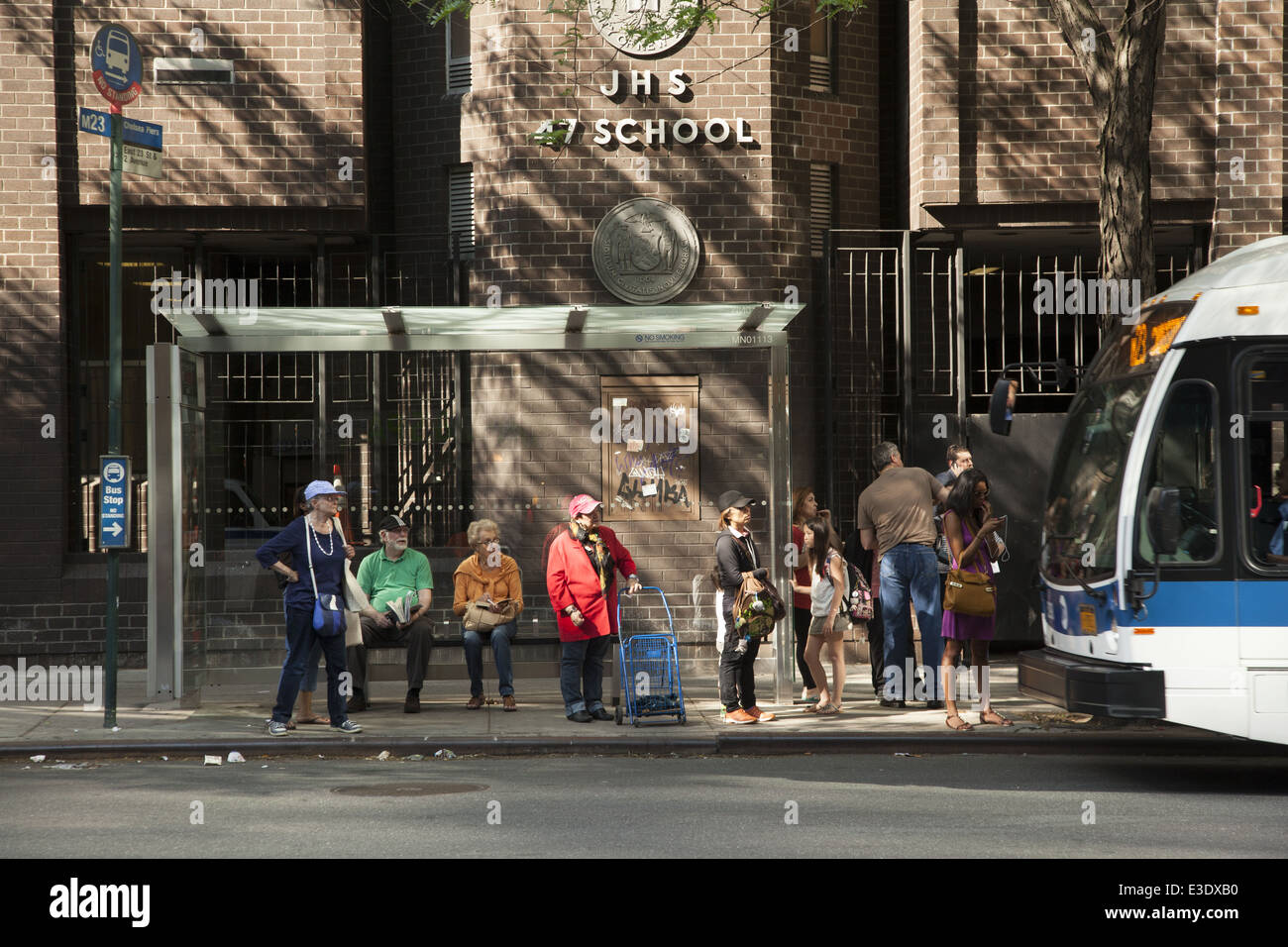 People wait for the crosstown bus along 14th St. in Manhattan, NYC. - Stock Image