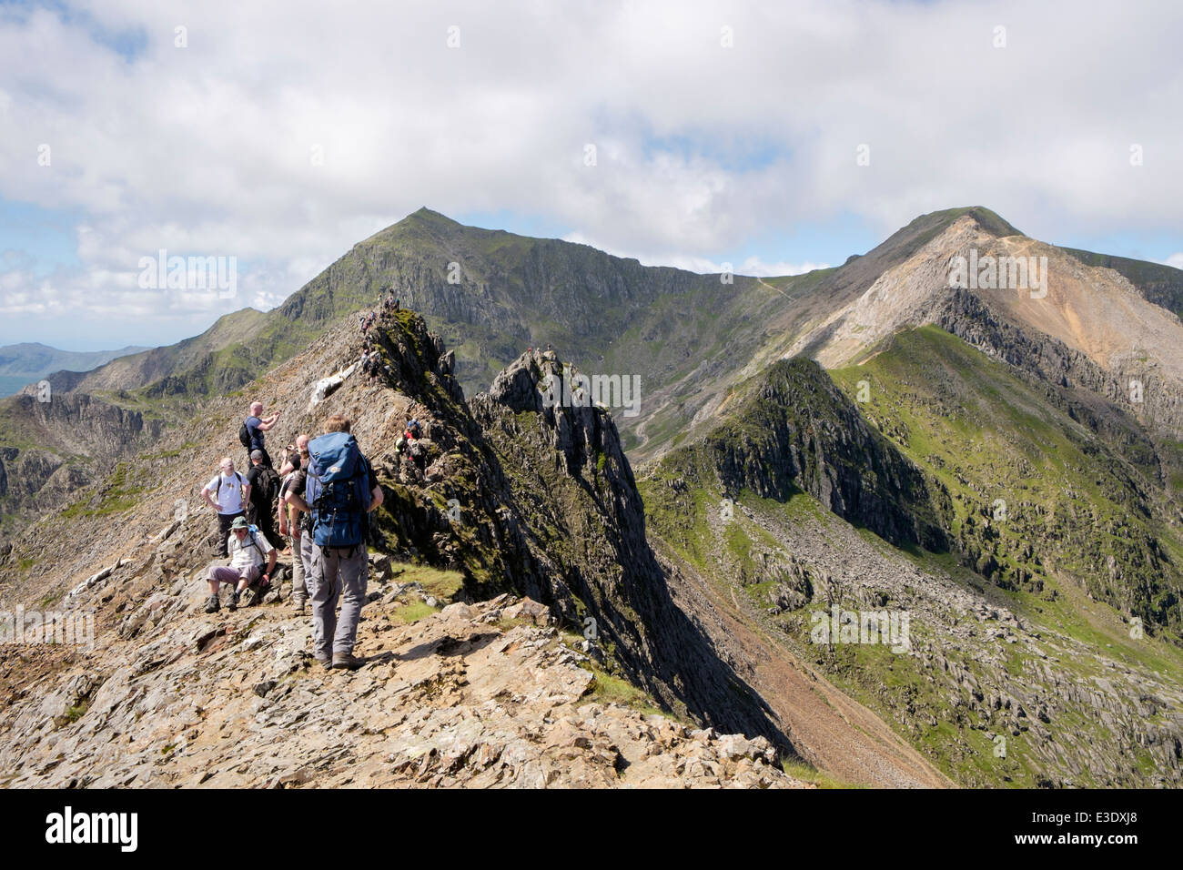 Walkers on Crib Goch ridge top scramble on the Snowdon Horseshoe with Crib y Ddysgl and Mt Snowdon peak in Snowdonia - Stock Image