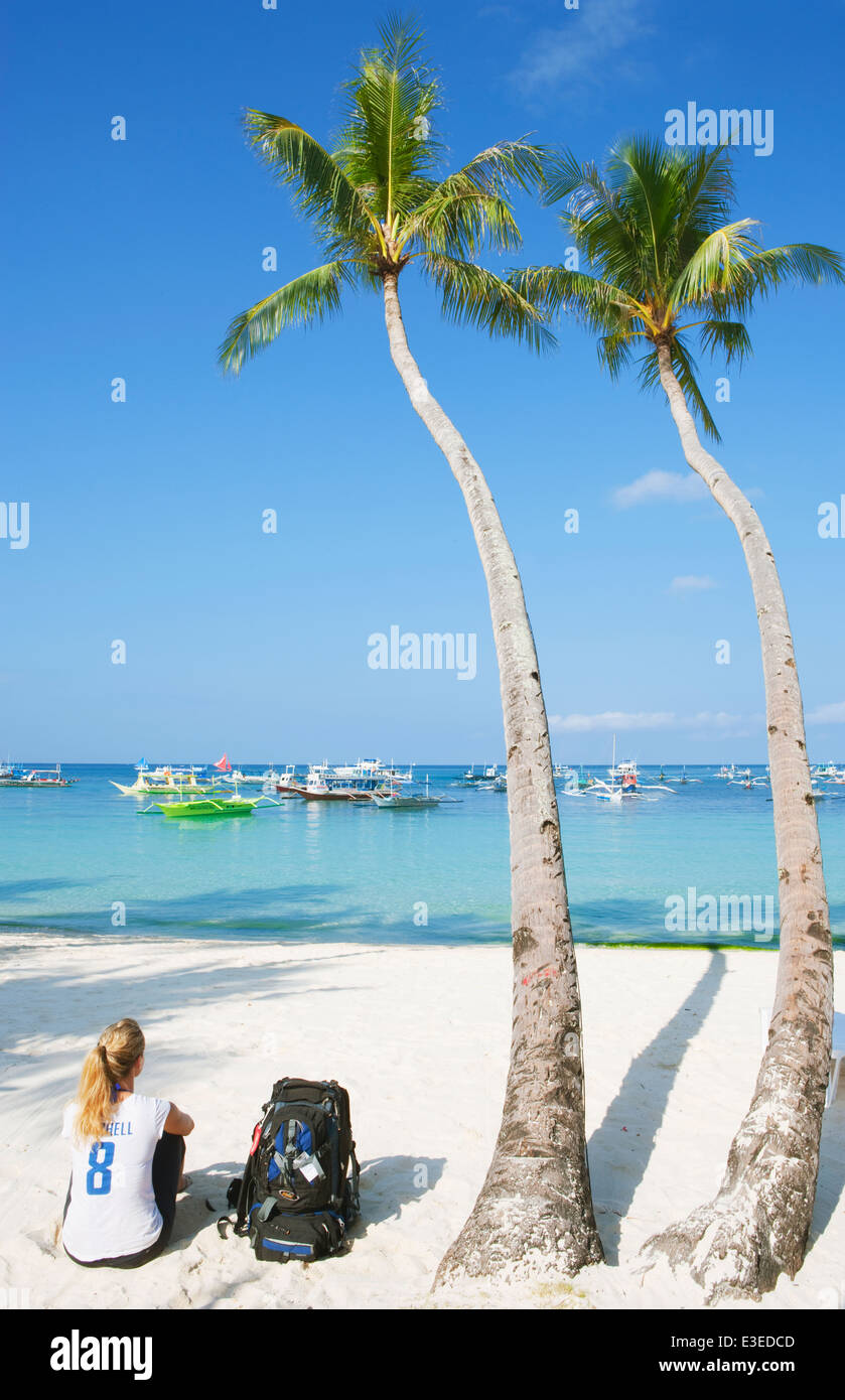 Young woman sitting on beach next to backpack Boracay; The Visayas; Philippines. - Stock Image