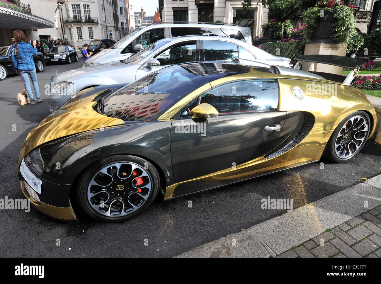 Passers By Stop To Check Out Two Flashy Cars Parked Outside The