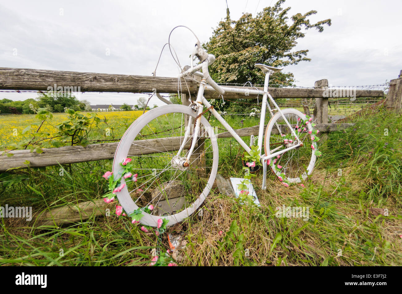 'Ghost Bike' on a rural road in tribute to a cyclist killed in a road traffic accident. - Stock Image