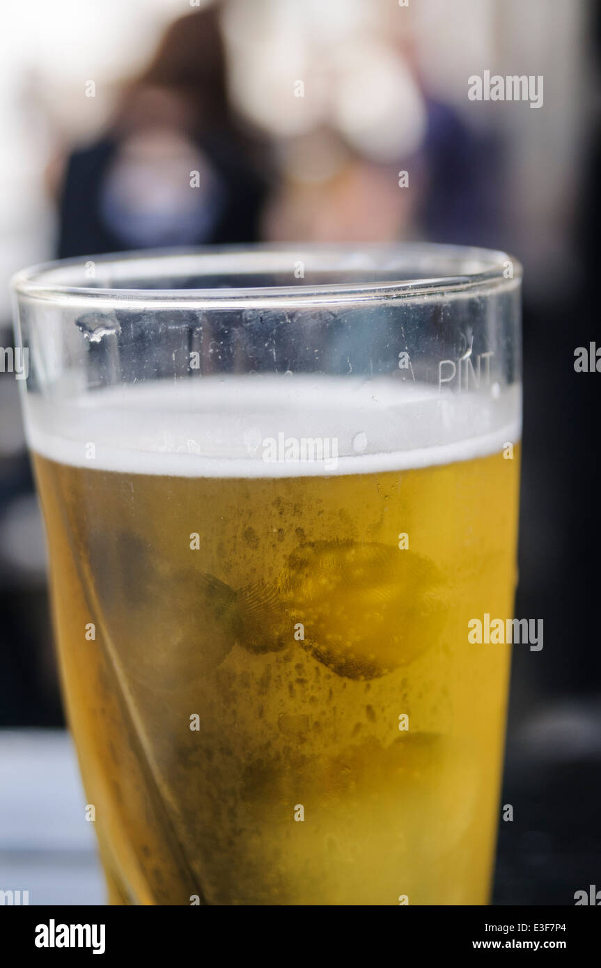 Pint of cider on an outside table at a pub. - Stock Image