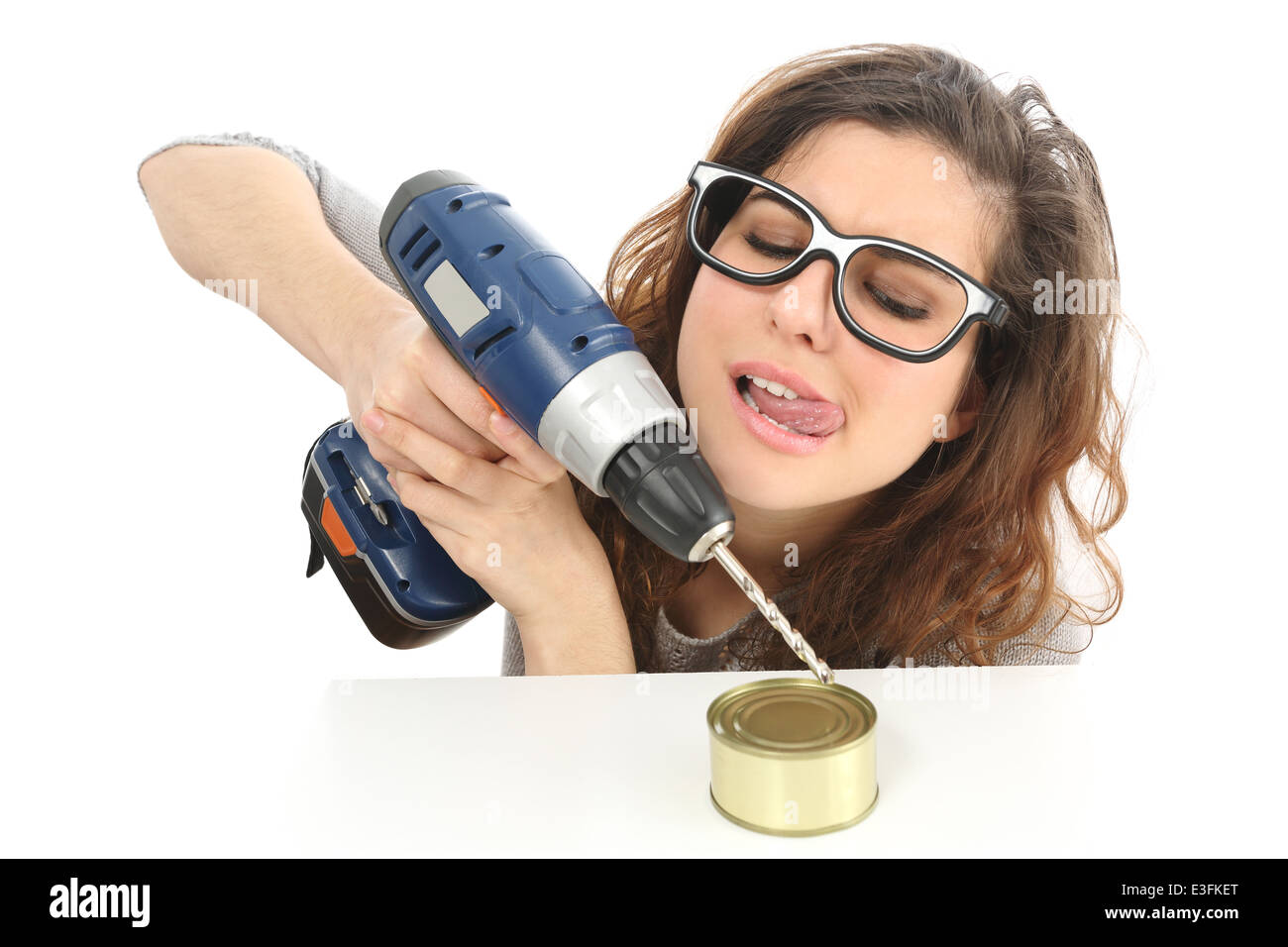 Funny geek girl trying to easy open a tin with a drill isolated on a white background - Stock Image