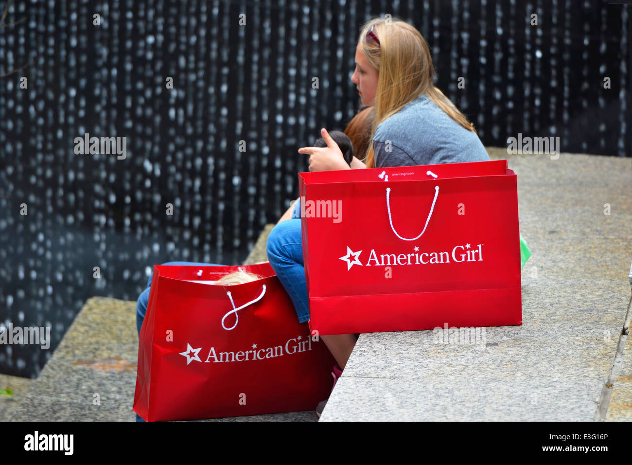 Girl sitting with American Girl Shopping Bags holding Doll, Chicago - Stock Image