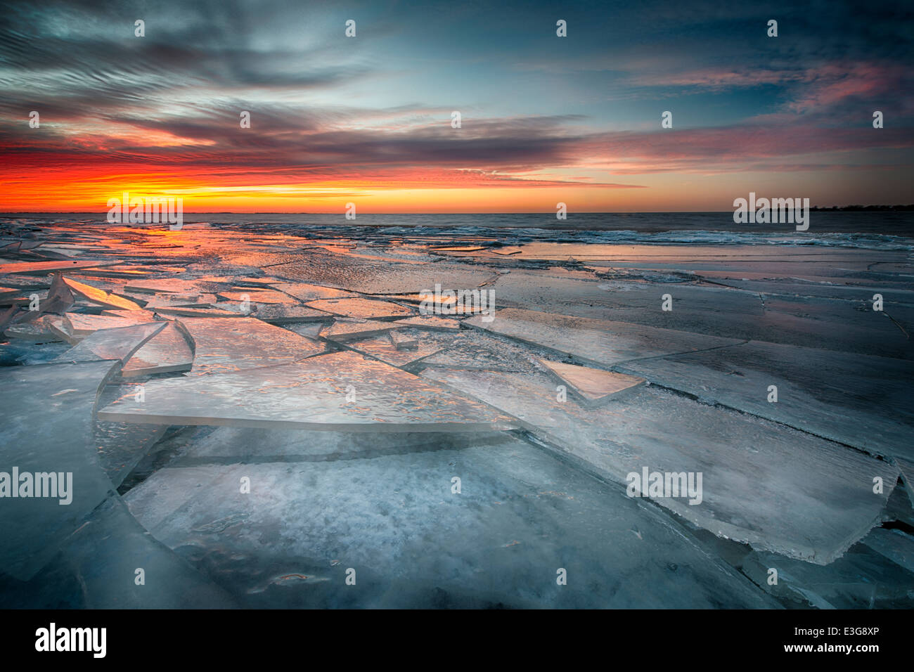 Ice sheets stack along the shores of Lake St. Clair in Southeast Michigan, reflecting the colors of twilight. - Stock Image