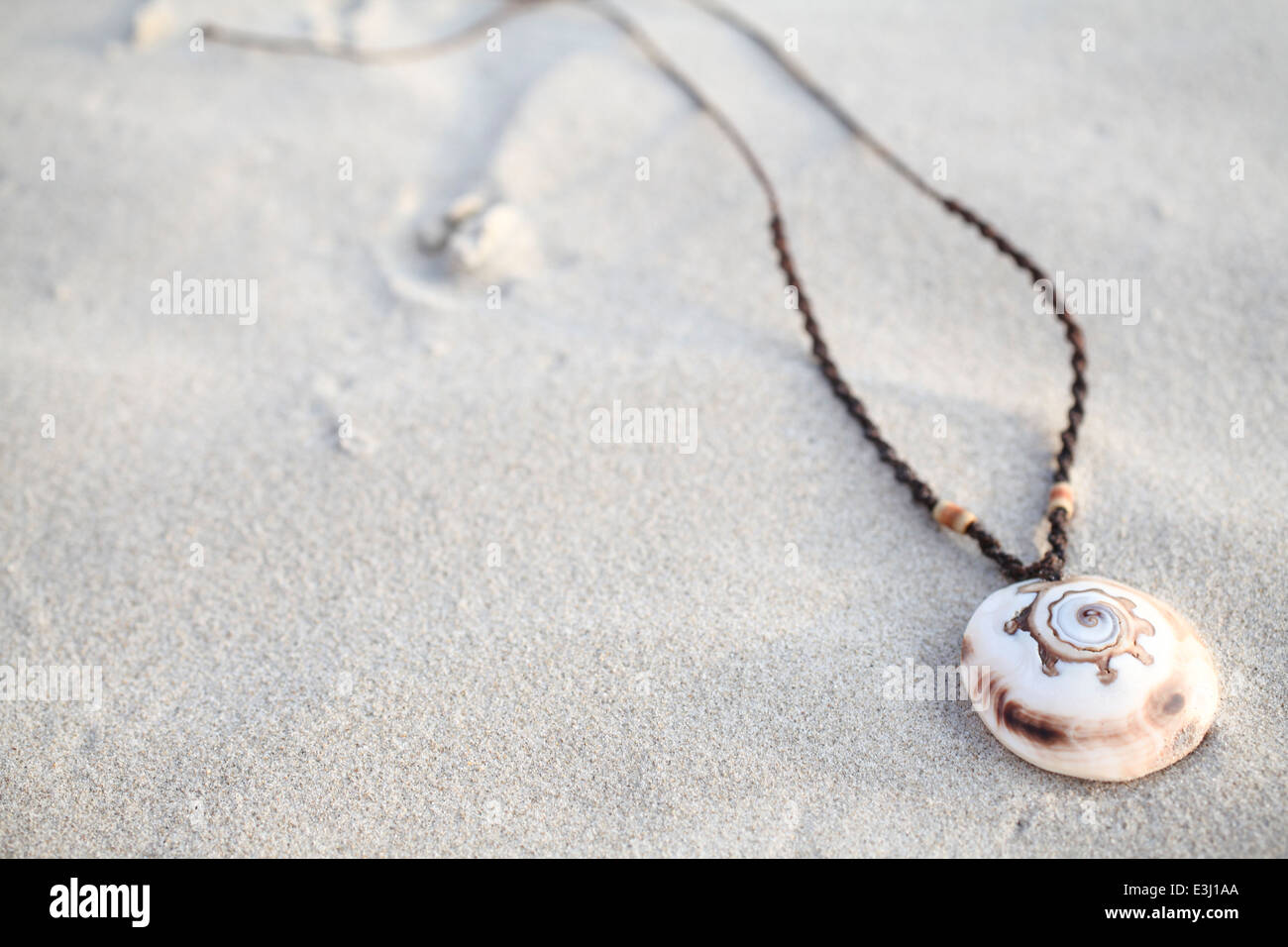 Seashell necklace on the sand - Stock Image