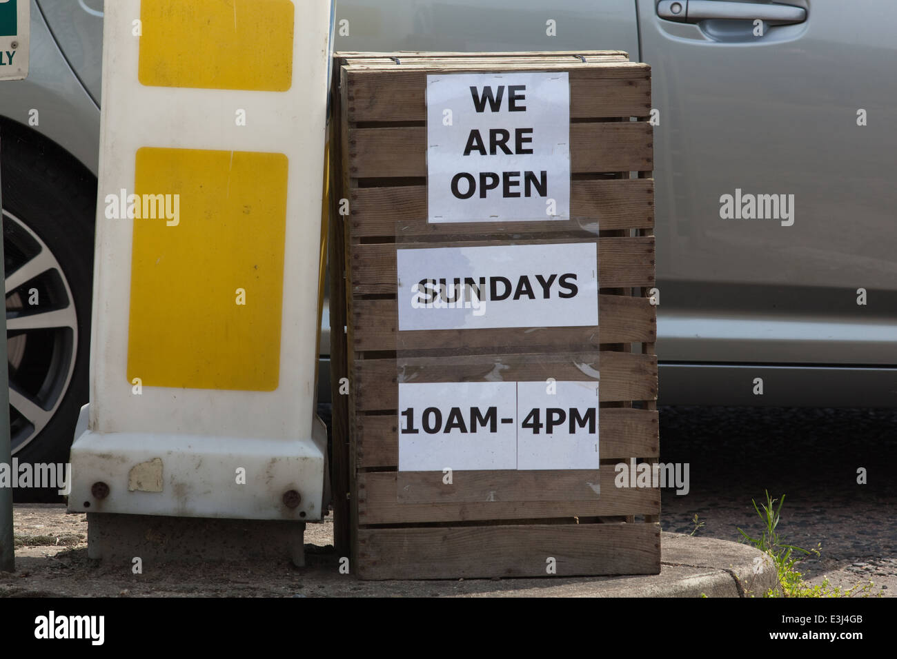 Sign out side a farm shop and garden centre. Announcing 'We are open on Sundays. 10 am - 4pm'. Change regarding - Stock Image