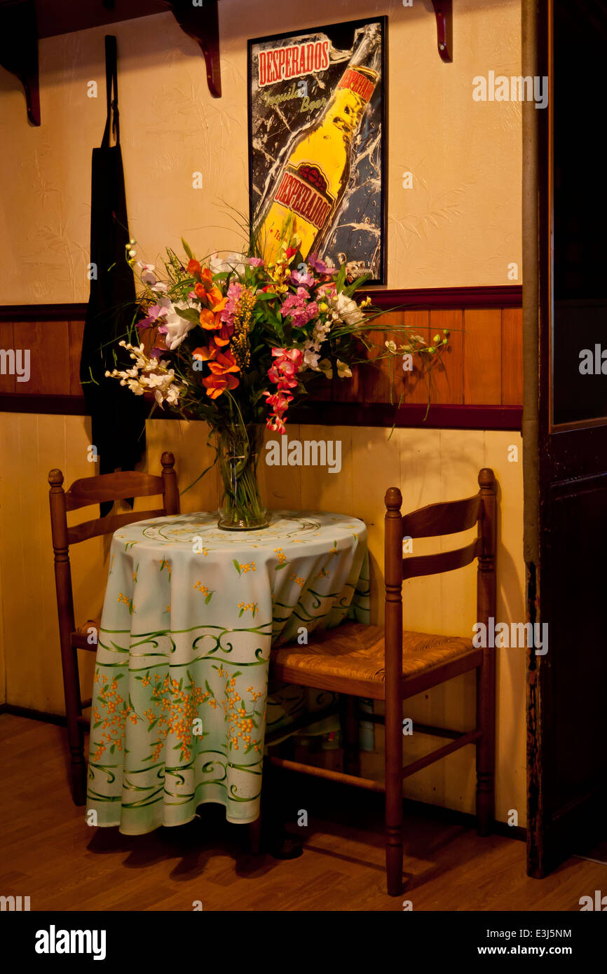 Large flower arrangement on table in French bistro / bar. Stock Photo