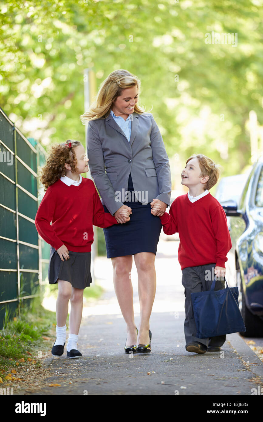 Mother Walking To School With Children On Way To Work - Stock Image