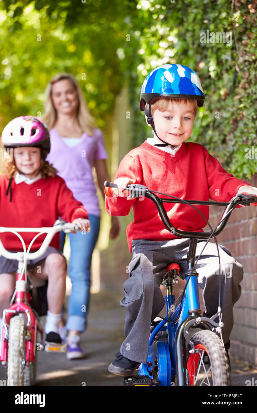 Children Riding Bikes On Their Way To School With Mother - Stock Image