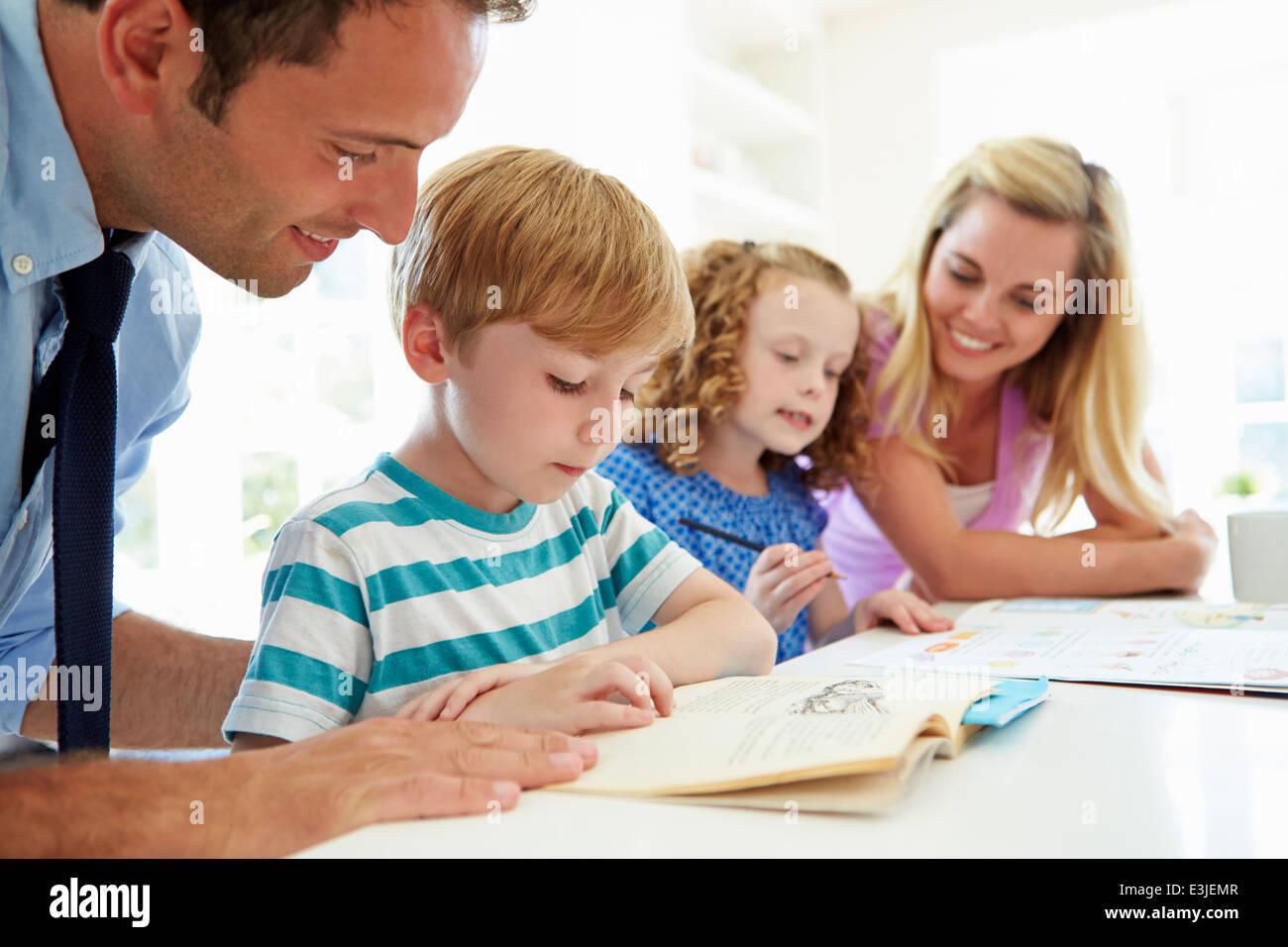Parents Helping Children With Homework In Kitchen - Stock Image