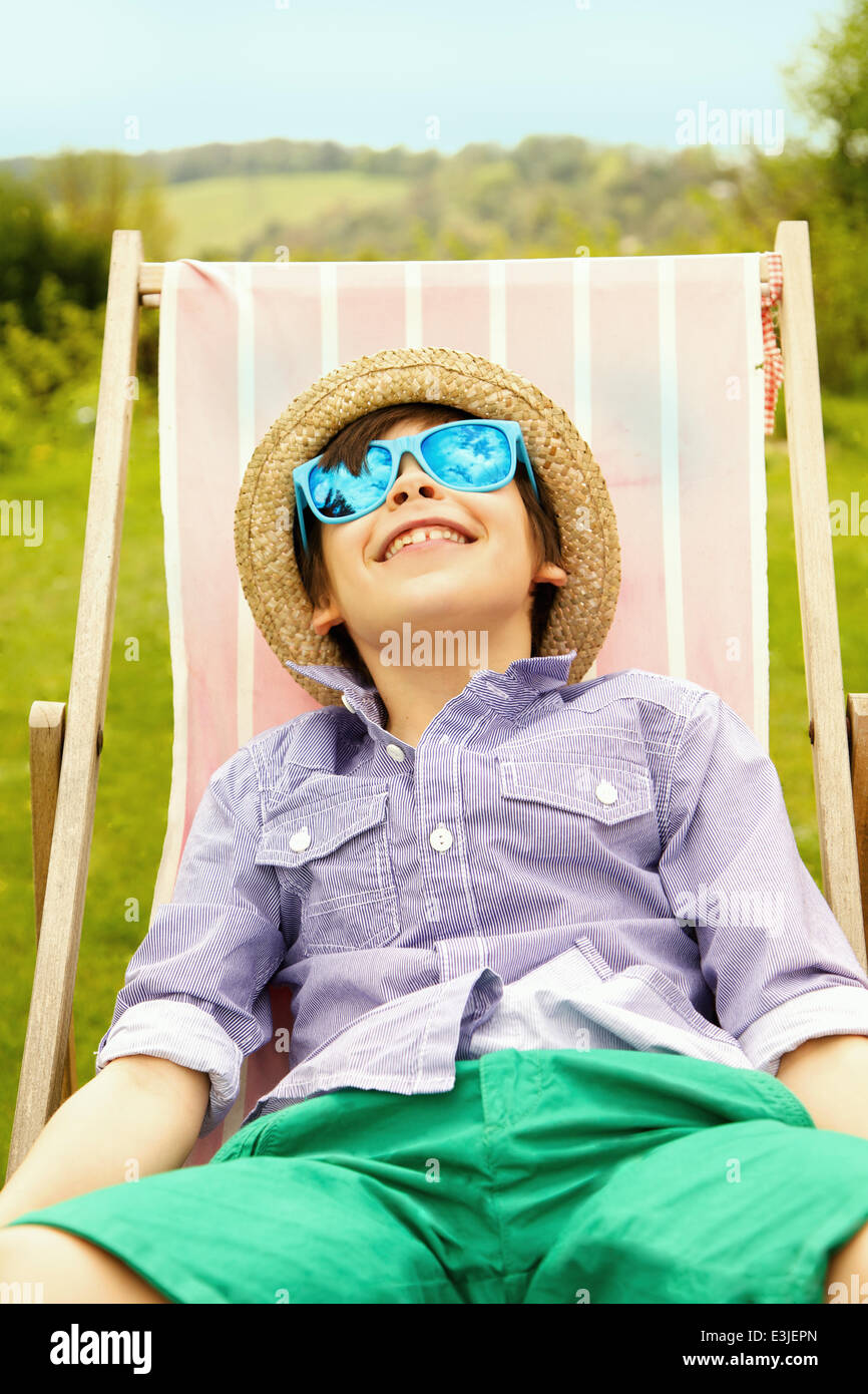 Smiling Boy Wearing Straw Hat and Sunglasses Sitting on Deck Chair Stock Photo