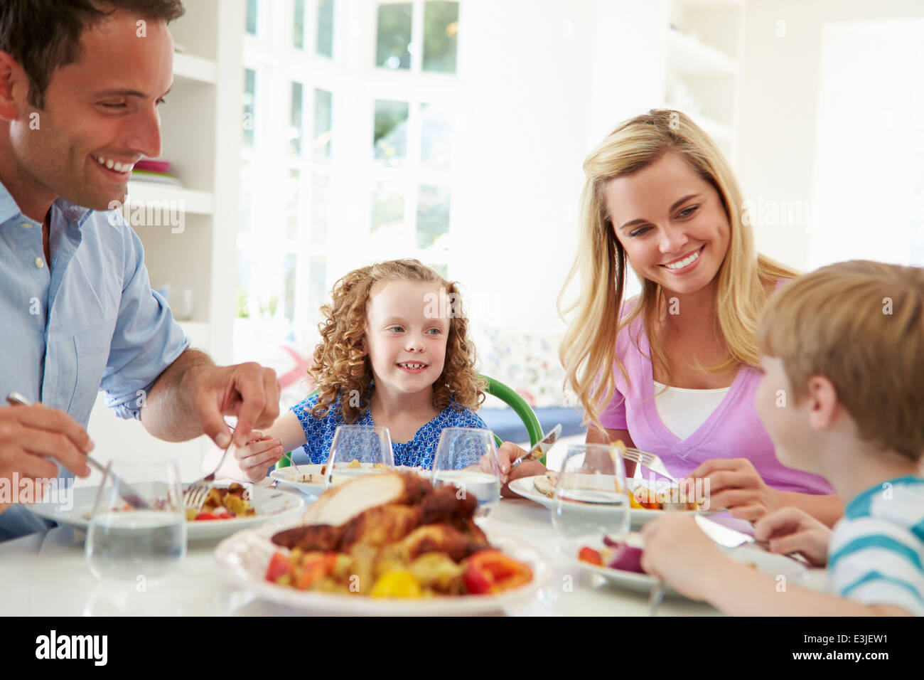 Family Eating Meal At Home Together - Stock Image