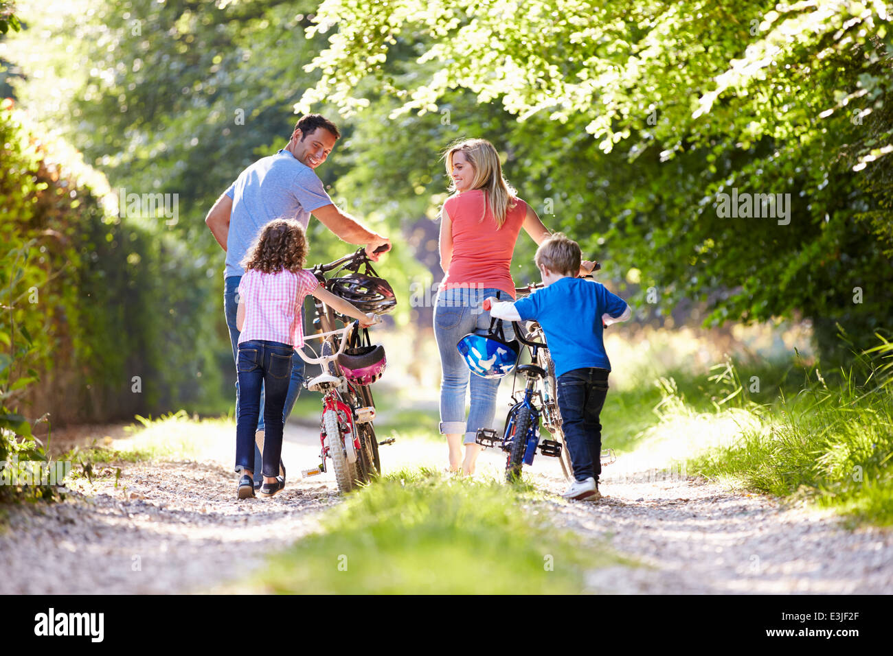 Family Pushing Bikes Along Country Track - Stock Image