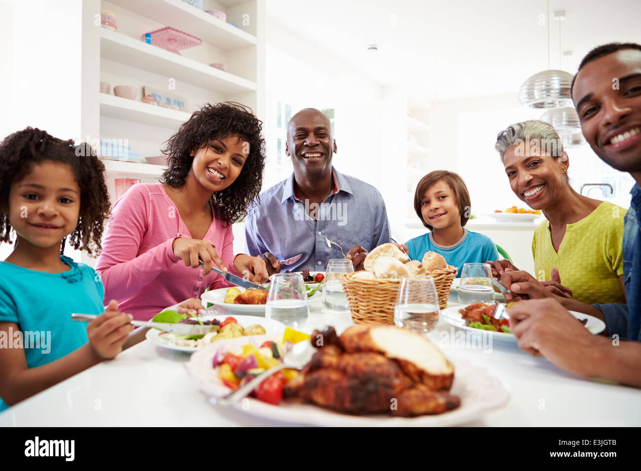 Multi Generation African American Family Eating Meal At Home - Stock Image