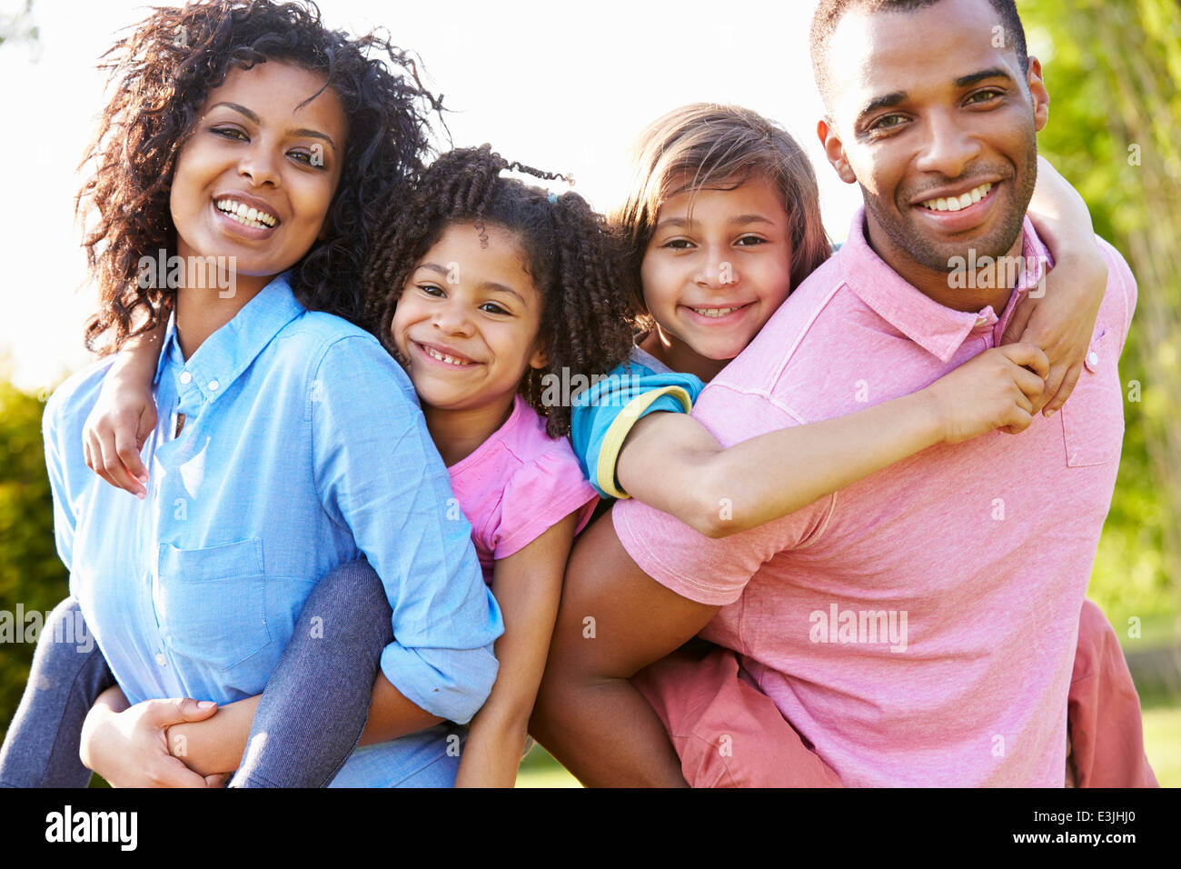 African American Parents Giving Children Piggyback Rides - Stock Image