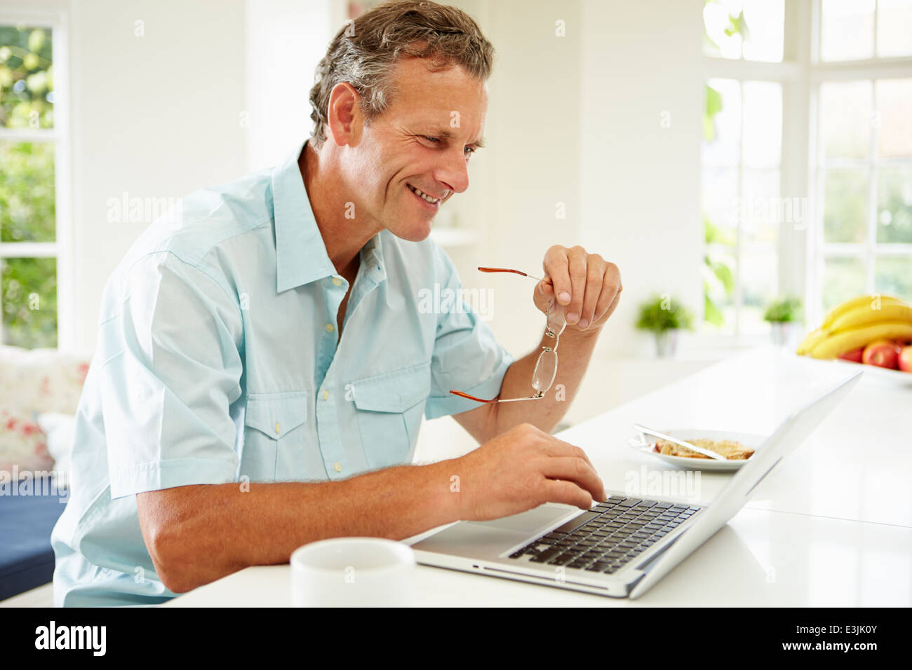 Middle Aged Man Using Laptop Over Breakfast - Stock Image