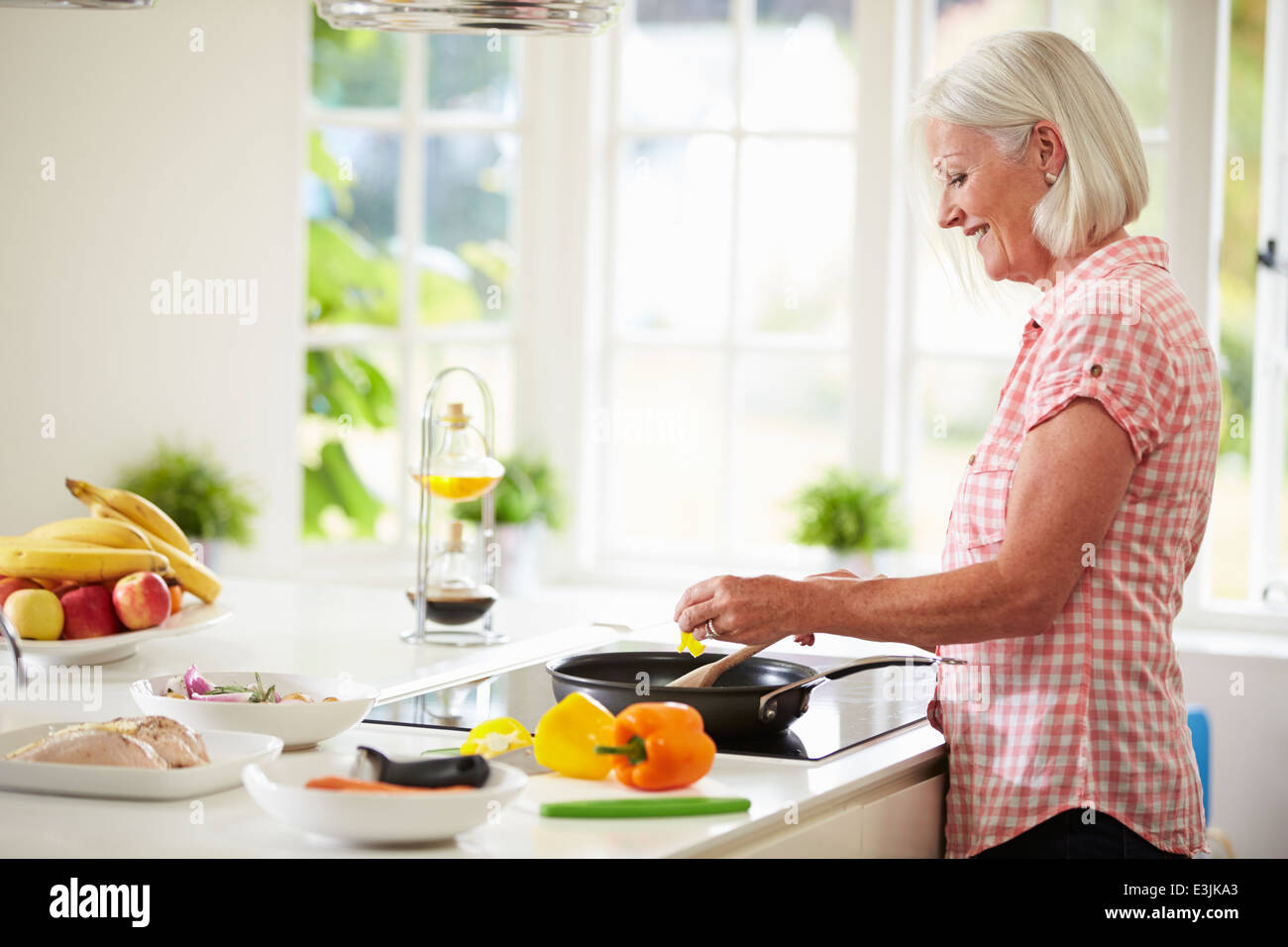 Middle Aged Woman Cooking Meal In Kitchen Stock Photo: 71095755 - Alamy