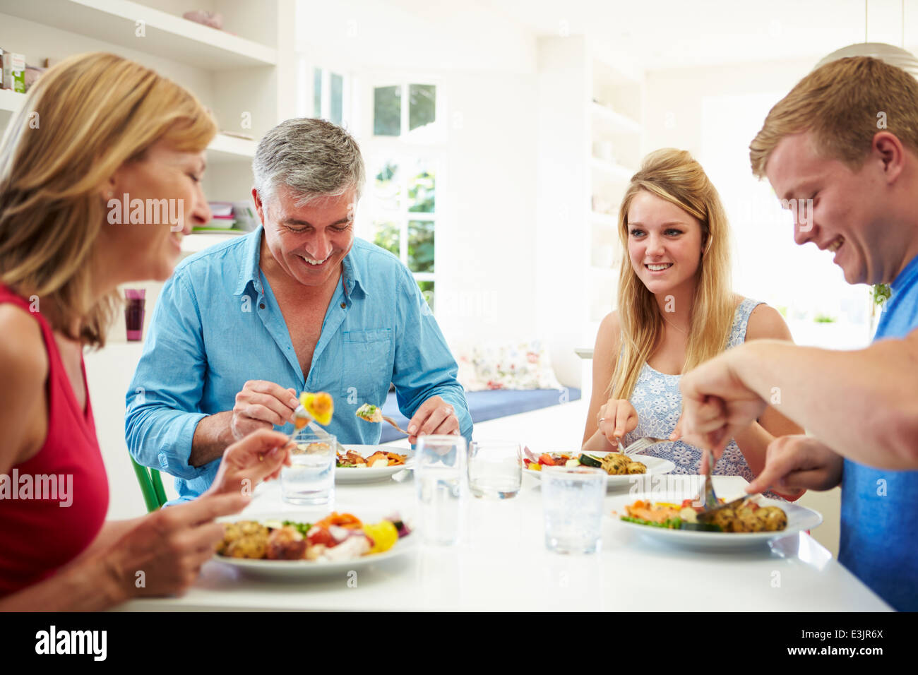 Family With Teenage Children Eating Meal At Home Together - Stock Image