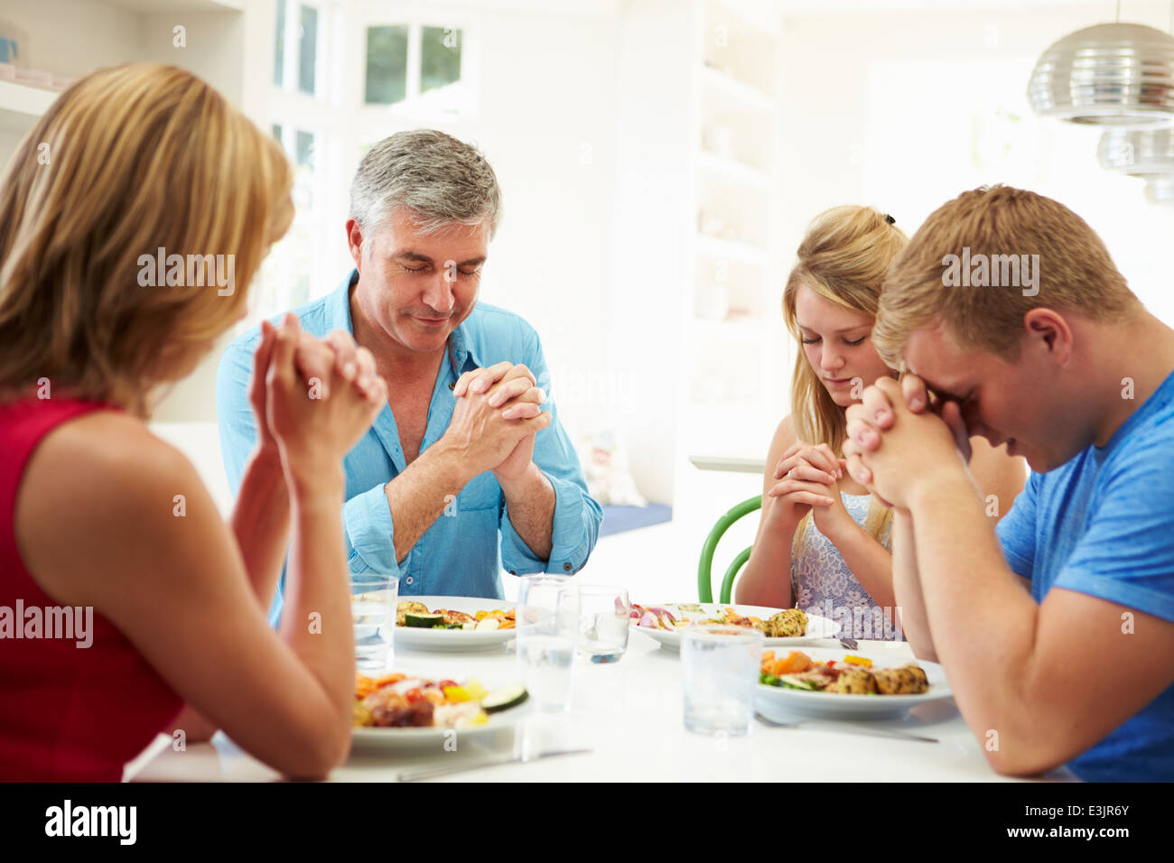 Family Saying Prayer Before Eating Meal At Home Together - Stock Image
