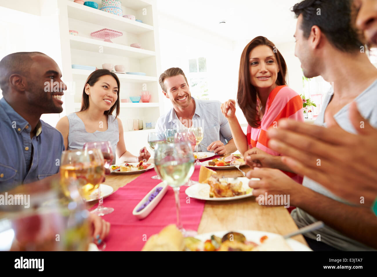 Group Of Friends Sitting Around Table Having Dinner Party - Stock Image